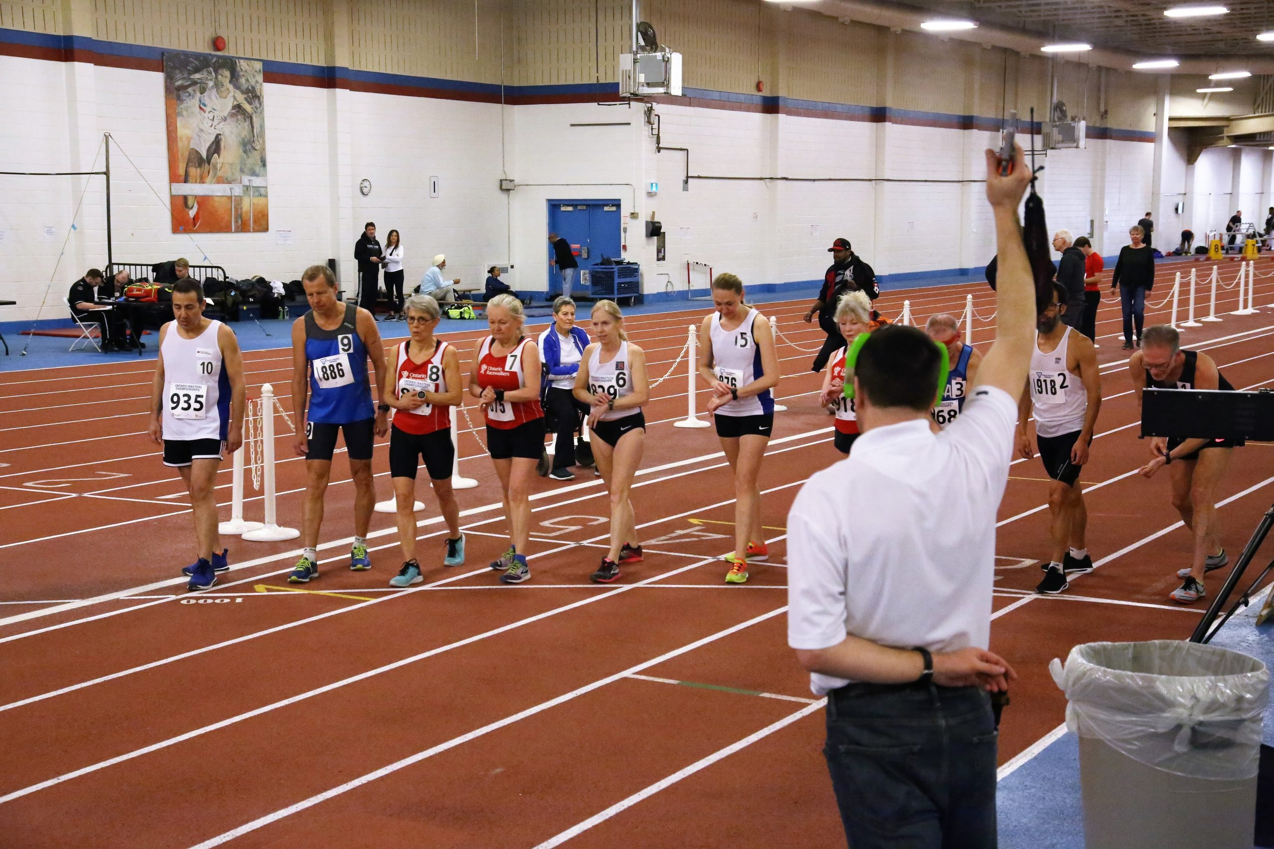 A group of race-walkers at the starting line at an indoor event